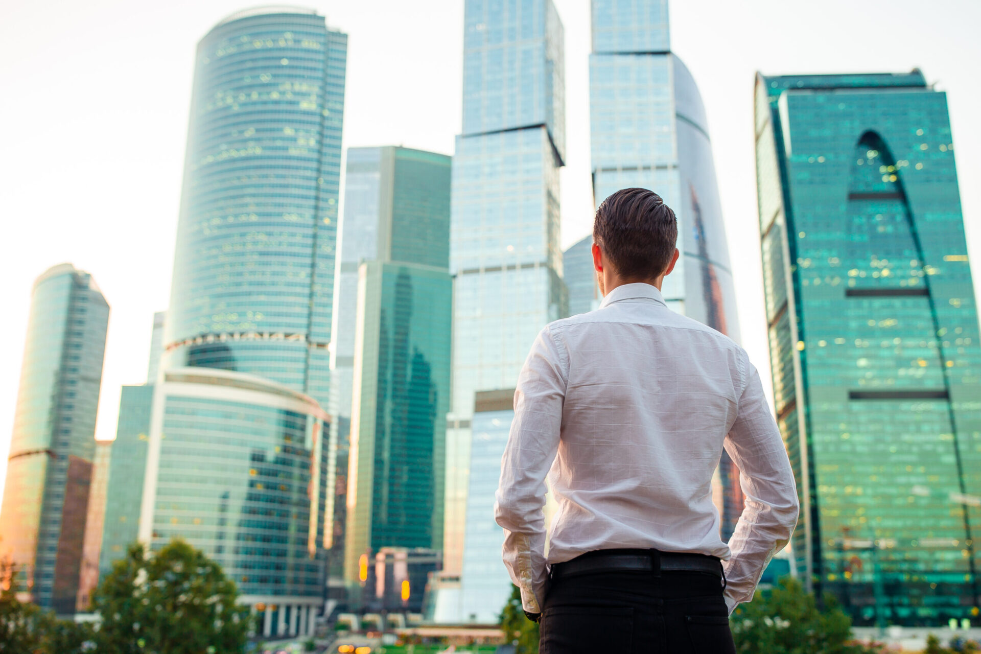 Back view of businessman looking on copy space while standing against glass skyscraper, young professional employee waiting for international partners outdoors near big company. Young man at sunset